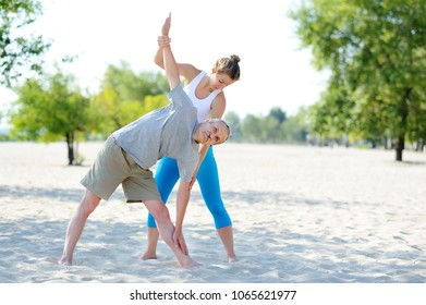Private yoga instructor helping senior man to practice triangle yoga pose