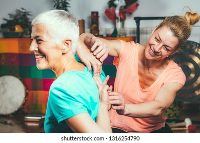 Private yoga instructor with senior woman doing yoga