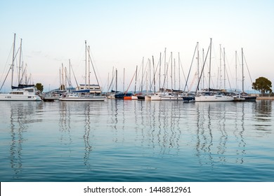 Privieza, Greece, June 2019. A look at the marina with sailing yachts at the pier in the seaside resort town. The calm sea and the view of the mountain tops of the neighboring island sunset. Tourism