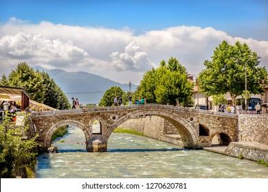Prizren, Kosovo - May 30th 2018 - Tourist and locals crossing a stone bridge, a famous spot of the old town of Prizren in Kosovo