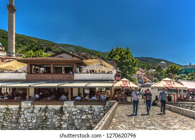 Prizren, Kosovo - May 30th 2018 - Tourist and locals crossing a stone bridge, a famous spot of the old town of Prizren with a restaurant in the background in Kosovo