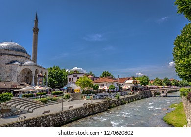 Prizren, Kosovo - May 30th 2018 - A wide river flowing in front of a mosque and restaurants in the old part of Prizren in Kosovo