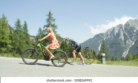 Pro biker gives up and walks along his road bicycle as blonde girl overtakes him effortlessly. Onlooking male biker stops and praises blonde woman pedaling up a steep hill on her cool electric bike.