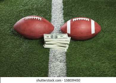 Pro and college style footballs with a pile of money on the line