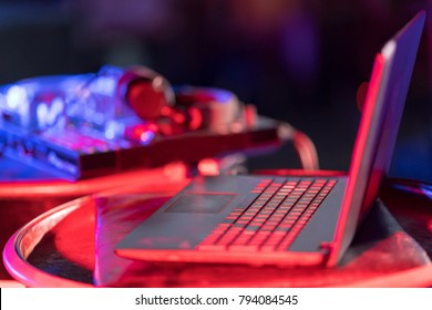 Pro DJ controller. The DJ console CD mp4 deejay mixing desk Ibiza house music party in nightclub with colored disco lights.