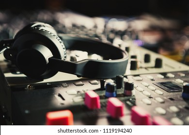 Pro dj headphones on sound mixer device in nightclub on stage.Professional audio equipment for disc jockey ti mix and play hip hop music tracks on concert in the club.Techno party background
