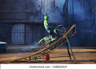 Pro motocross rider riding fmx motorbike, jumping performing extreme stunt. Professional biker jumps
