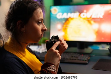 Pro player sitting on gaming chair at desk and losing space shooter video games using console. Woman streaming online videogames for esport tournament in room with neon lights