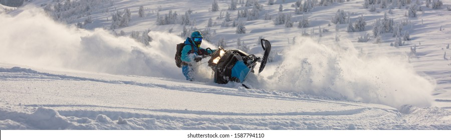 Pro snowmobiler makes a turn and lets a flurry of snow spray from under the caterpillar. sports snowmobile in the mountains. bright skidoo motorbike and suit without brands. Winter fun. panoramic view