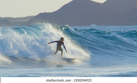Pro surfboarder riding big barrel ocean waves in beautiful Fuerteventura. Cheerful young man in wetsuit skilfully carving breaking waves in the Canaries. Surfer catching waves on cool active holiday