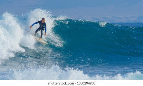 Pro surfer on active summer vacation enjoying sunny day surfing in clear ocean water of Fuerteventura. Extreme male surfboarder looking around sunny Canary Islands while carving a clear blue wave.