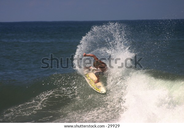 Pro surfer throwing spray at Pipeline, Oahu