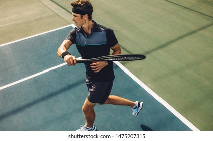 Pro tennis player practicing forehands on a club hard court. Young male tennis player playing on a club tennis court.