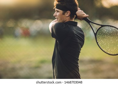 Pro tennis player practicing on a club court. Young male tennis player playing on a club tennis court.