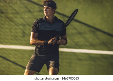 Pro tennis player practicing tennis on a club court. Young male tennis player playing on a hard court.