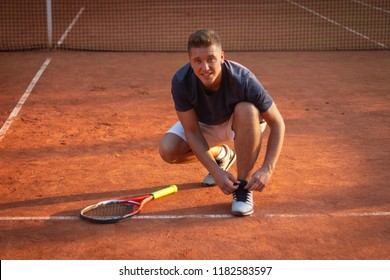 Pro tennis player tying sneakers on court for match