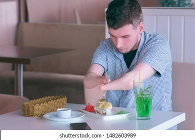 Problem of adaptation to usual life guy without wrists. Disabled man with two amputated stump hands eats sushi rolls in cafe with fork. Independent Invalid person with disabilities.