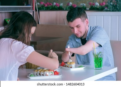 Problem of adaptation to usual life guy without wrists. Disabled man with two amputated stump hands on date with woman in cafe eats rolls talks with girl. Independent Invalid person with disabilities.