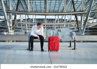 problem in the airport, tired man waiting in the terminal with luggage
