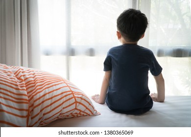The Problem of Child Development:A little boy sitting by the bed looking through the window Absent-minded. Recognizing Developmental Delays in Children, Autism awareness, Psychological trauma.