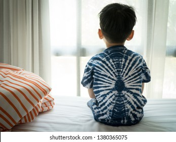 The Problem of Child Development:A little boy sitting by the bed looking through the window Absent-minded. Recognizing Developmental Delays in Children, Autism awareness, Psychological trauma