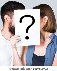 Problem in couple, question mark. Couple holding paper question mark. Anonymous, man and woman question. Kiss couple, incognita. Problems and solutions. Couple in quarrel. Quarrel between people.