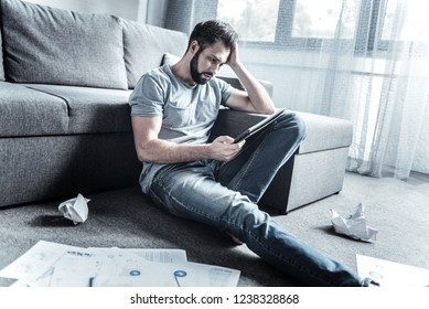 Problem decision. Serious young man stretching leg while sitting on the floor and looking at his gadget
