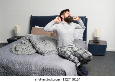 Problem with early morning awakening. Get up early. Tips for waking up early. Man bearded hipster sleepy face pajamas waking up bedroom interior. Daily schedule for healthy lifestyle. Rest and relax.