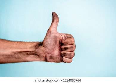 Problem with social media concept. Dirty hand making thumb up gesture on blue background.