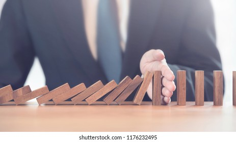 Problem Solving, Close up hand of businessman stopping falling blocks on table.