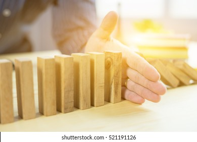 Problem Solving,businessman stop effect of dominoes continuous toppled with hand at desk,retro style image executive and risk control concept,selective focus,vintage color