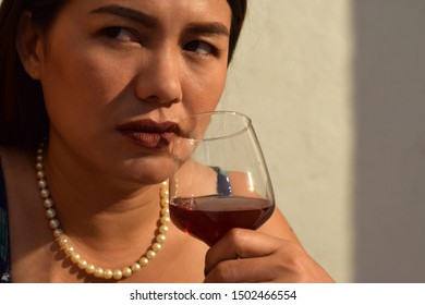 Problematic, resentful beautiful middle aged woman holding wine glass close to her lips