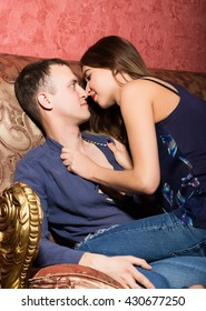 problems in family relationships, a young couple sitting on the couch. man hurt, woman sits astride a man and kisses him