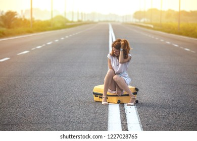 problems in the journey. the girl is sitting on a yellow suitcase on the dividing strip on the road.