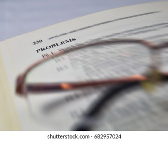 problems on a school and university textbook with glasses