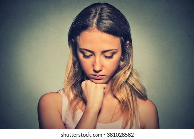 problems. Sad woman isolated on gray wall background