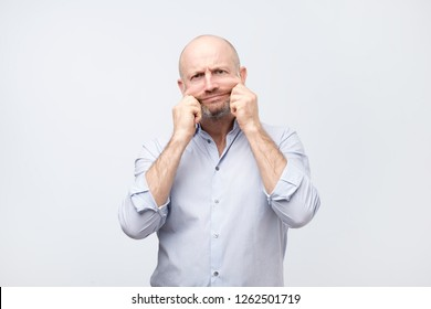 Problems with skin and wrinkles. Handsome caucasian man in white shirt stretching his skin on face. Extra skin on the face after losing weight