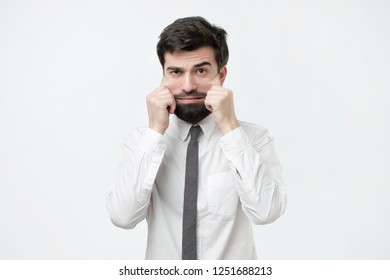 Problems with skin and wrinkles. Handsome spanish man in white shirt stretching his skin on face. Extra skin on the face after losing weight