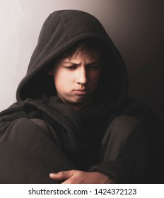 Problems of teenagers. Portrait of a sad teen boy in a dark key.