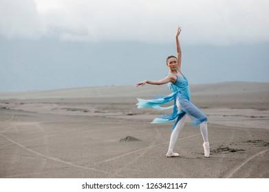 Probolinggo, East Java / Indonesia - January 28, 2012 : A ballerina with blue dress dancing at whispering desert Bromo National Park. Ballerina dancer concept.