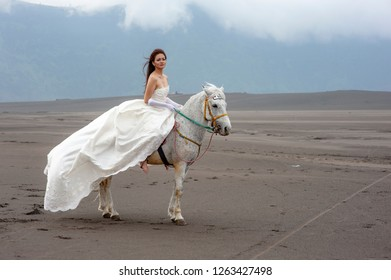 Probolinggo, East Java / Indonesia - January 28, 2012 : Beautiful girl with whithe dress and horse at whispering desert Bromo National Park. Ballerina dancer concept.