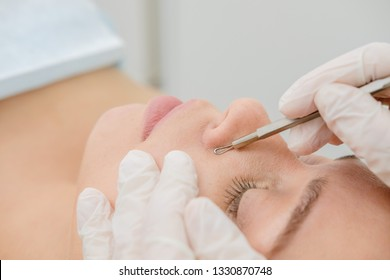 Procedure for cleaning skin with steel tool from blackheads and acne. Deep cleansing of the female face with blackhead remover in the beauty salon. Cosmetologist making receiving cleansing therapy