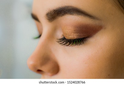 The procedure for eyelash extensions and nude makeup. Big eyes closed beautiful girls with green eyelashes.