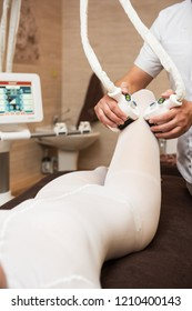 Procedure laser lipolysis of the woman hips in a beauty center.