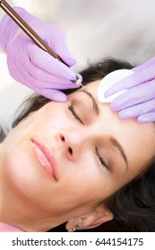 Procedure of making permanent makeup of eyebrows, close-up portrait of woman face and cosmetologists hands in gloves holding needle.