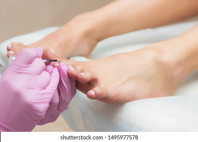 Procedure of pedicure in beauty salon. Nail polishing with nail polish. Closeup photo
