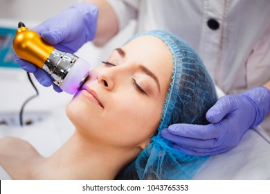 The procedure of photoepilation in the beauty salon. A young woman is removed unwanted hair on her face. Hardware cosmetology. Microcurrent therapy. Close up