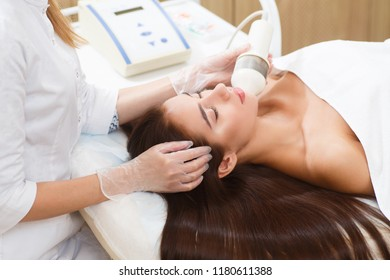 The procedure of photoepilation in the beauty salon. A young wom
