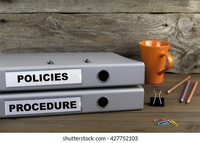 Procedure and Policies - two folders on wooden office desk