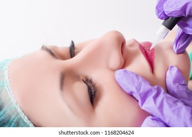 Procedure of professional applying permanent makeup on woman lips. Young beautiful girl getting tattoo in beauty salon. Close up, selective focus